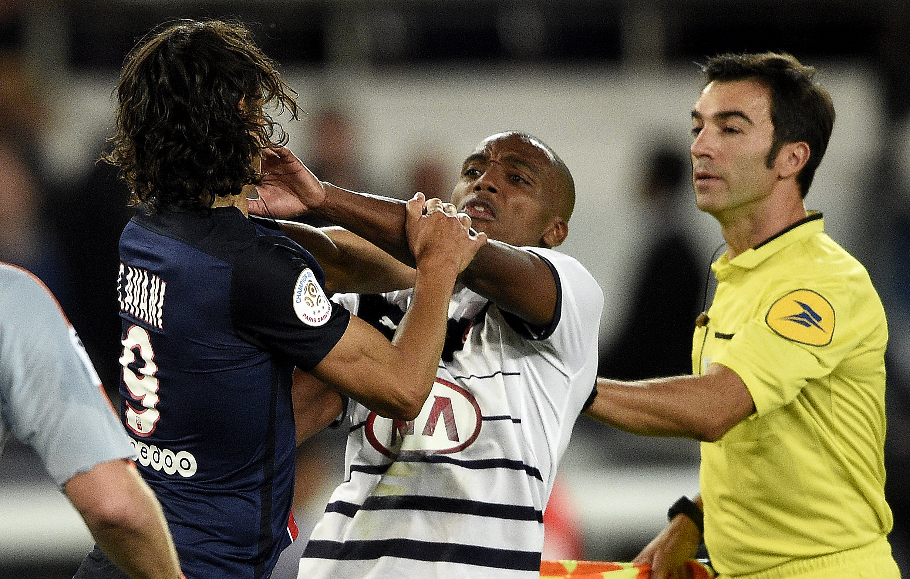 Paris Saint-Germain's Uruguayan forward Edinson Cavani (L) scuffles with Bordeaux's French midfielder Nicolas Maurice-Belay (C) at the end of the French L1 football match between Paris Saint-Germain (PSG) and Bordeaux at the Parc des Princes stadium in Paris on September 11, 2015. AFP PHOTO / FRANCK FIFE        (Photo credit should read FRANCK FIFE/AFP/Getty Images)