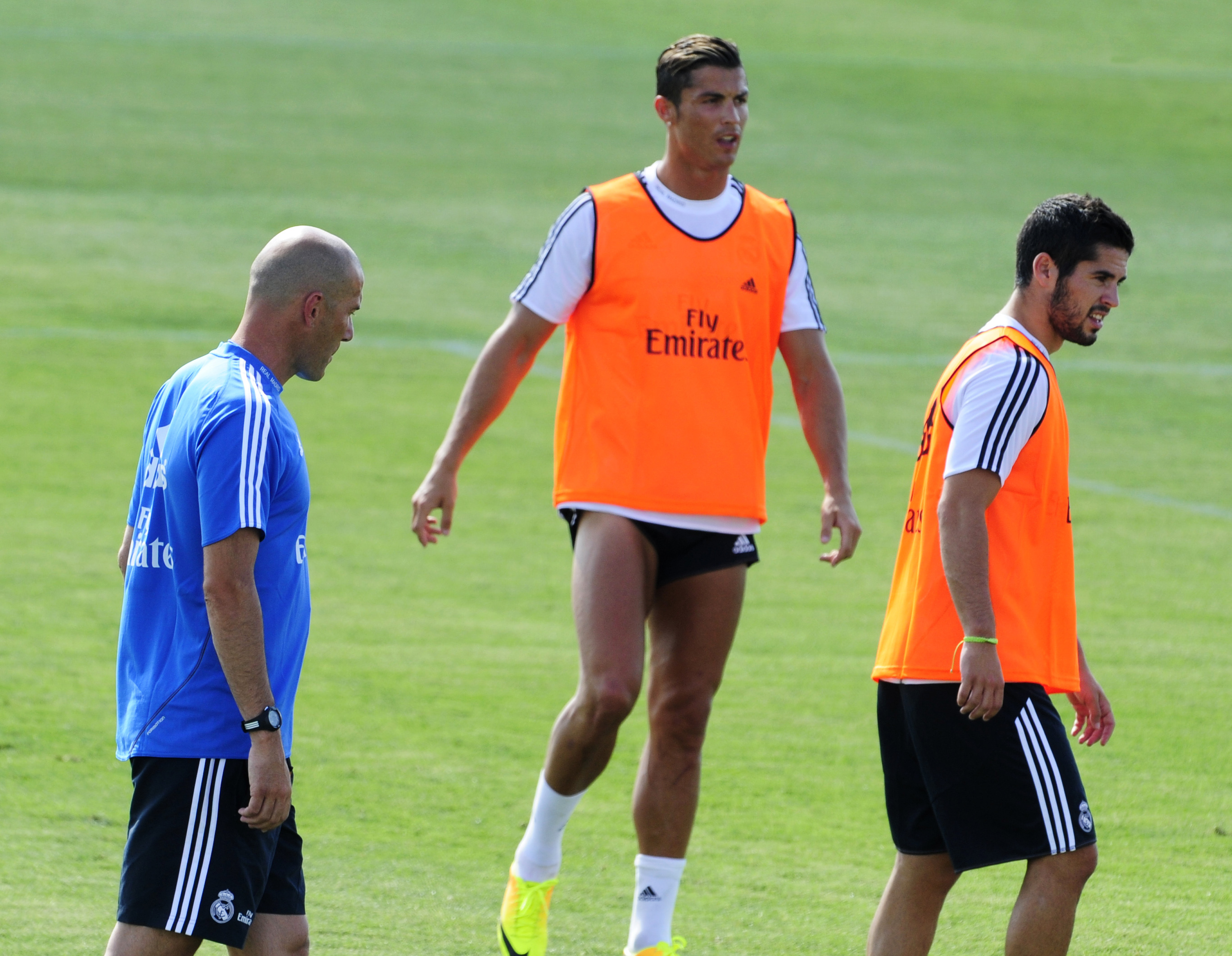 (L-R) Real Madrid's French assistant coach Zinedine Zidane, Real Madrid's Portuguese forward Cristiano Ronaldo and Real Madrid's midfielder Isco take part in the first pre-season training session at the Valdebebas training ground in Madrid on July 15, 2013.  AFP PHOTO / DOMINIQUE FAGET        (Photo credit should read )