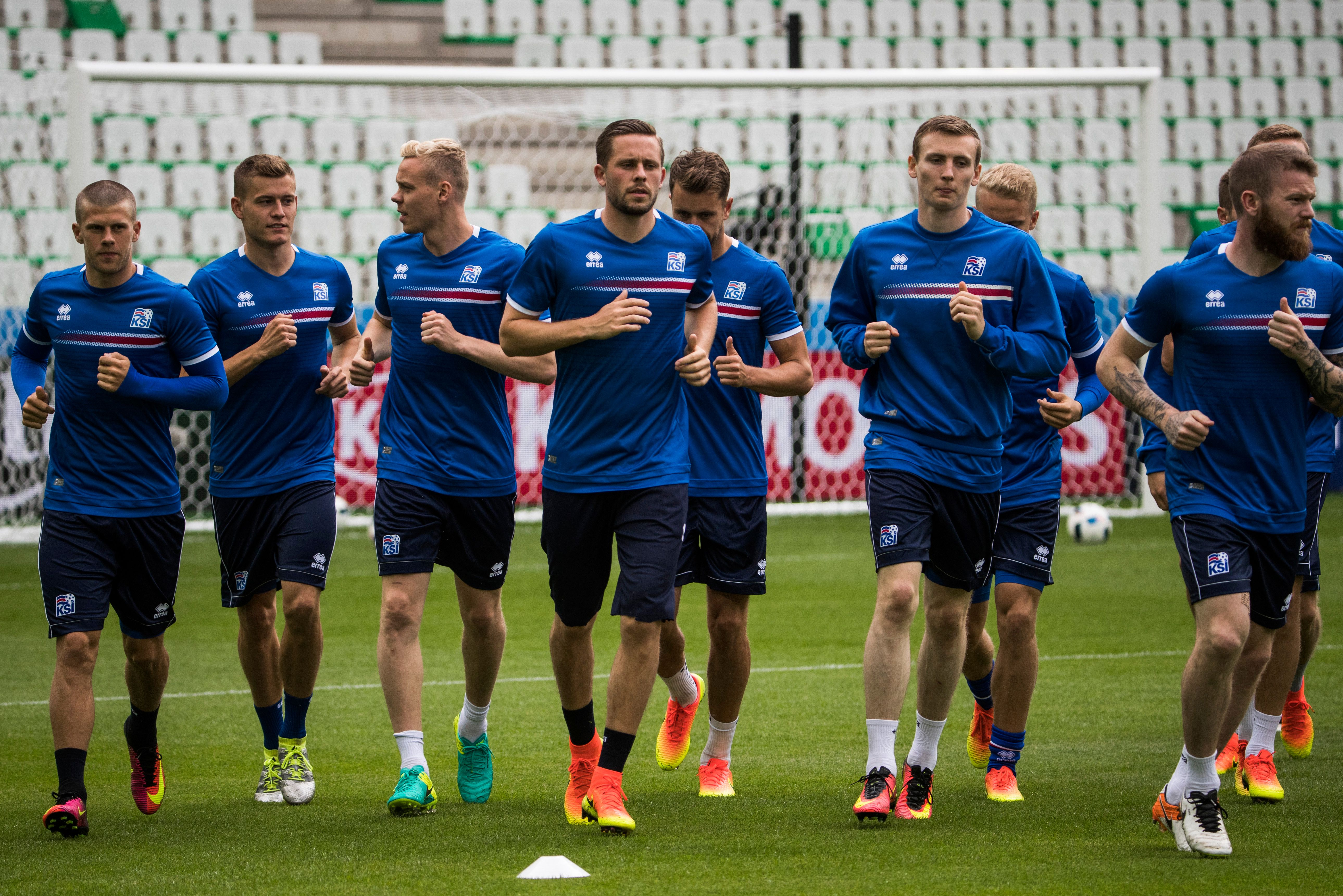 Iceland's midfielder Gylfi Sigurdsson (4th L) and team mates warm up during a Euro 2016 training session at the Geoffroy-Guichard stadium in St Etienne, on June 13, 2016, on the eve of their opening match against Portugal. / AFP / ODD ANDERSEN        (Photo credit should read )