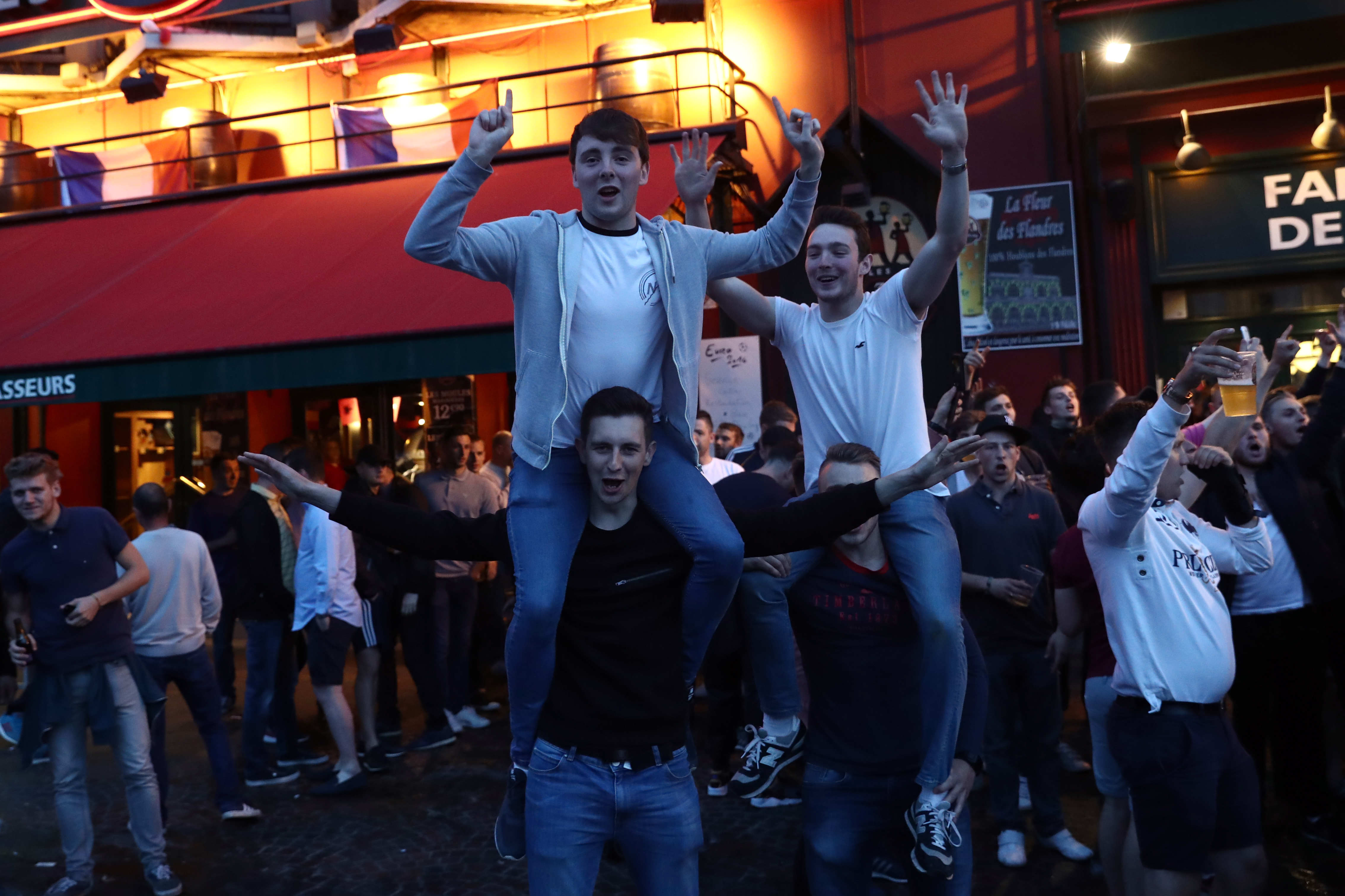 LILLE, FRANCE - JUNE 14:  English football fans chant and drink outside a pub as they gather ahead of the England v Wales game Thursday, on June 14, 2016 in Lille, France. Football fans from around Europe have descended on France for the UEFA Euro 2016 football tournament.  (Photo by Carl Court/Getty Images)